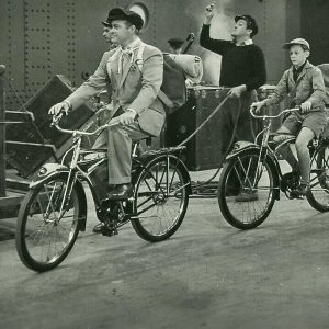 Bob Hope, Orley Lindgren and Boy Scouts ride bikes.
