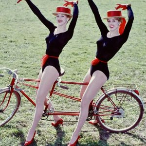 Alice and Ellen Kessler ride a bike.