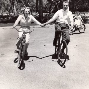 June Allyson and Dick Powell ride bikes, hold hands.