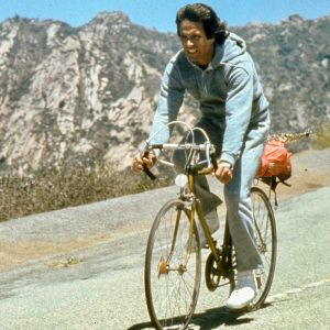 Warren Beatty rides a bike.