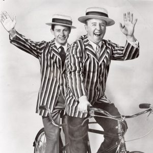 Eddie Fisher and George Gobel ride a bike.