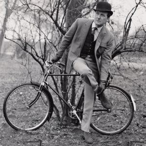 Patrick Macnee rides a bike.