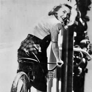 Susanna Foster rides a bike.