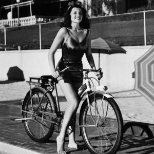Rita Hayworth rides a bike, poolside.