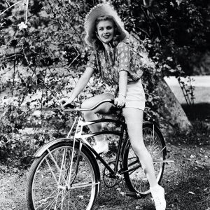Ginger Rogers rides a bike.