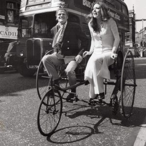 "Keith Mitchell and Diana Rigg ride a ""honeymoon"" bike."