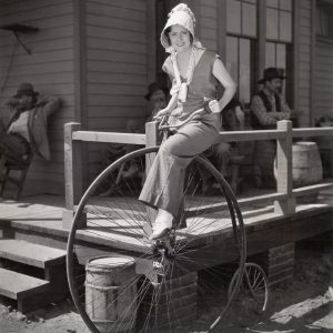 Irene Dunne rides a high-wheel bike.