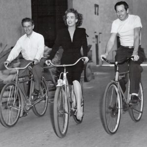 Curtis Bernhardt, Joan Crawford and Jack Daniels ride bikes.