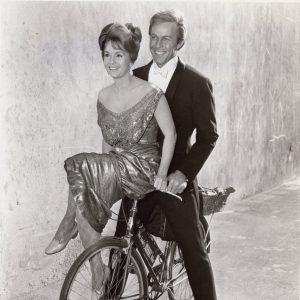 Debbie Reynolds and Harve Presnell ride a bike.
