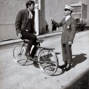 Fess Parker rides a bike — backwards.