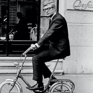 Michael Caine rides a bike.