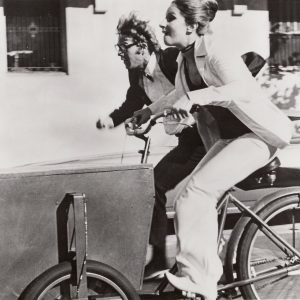 Barbra Streisand rides a delivery trike, Ryan O'Neal runs alongside.