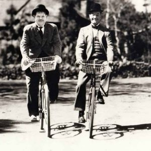 Oliver Hardy and Stan Laurel ride bikes.