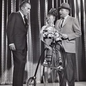 Effie Klinker rides a bike, Ed Sullivan and Edgar Bergen look on.