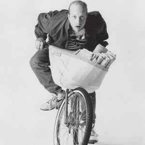 Chris Elliott rides a bike.