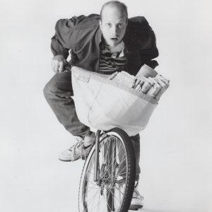 Chris Elliott rides a bike.
