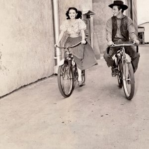 Donna Reed and William Lundigan ride bikes.