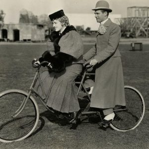 Marion Davies and Lawrence Gray ride a bike.