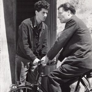 Marcel Pagliero rides a bike, Marcel Mouloudji stares him down.