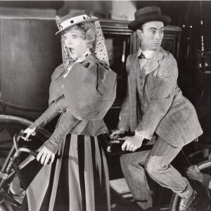 Marion Davies and George Chandler ride a bike.