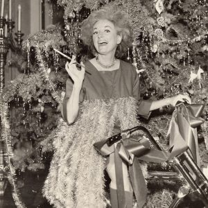 Phyllis Diller rides a Christmas bike.