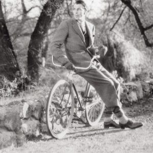 Gary Cooper rests on a bike.
