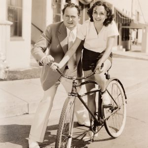Andrea Leeds rides a bike, Edward Arnold assists.