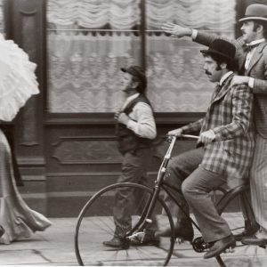 Elliott Gould and James Caan ride a bike.