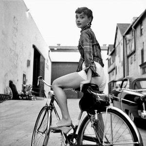 Audrey Hepburn rides a bike.