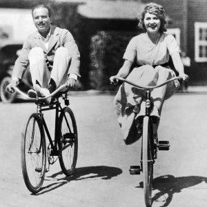 Douglas Fairbanks and Mary Pickford ride bikes.