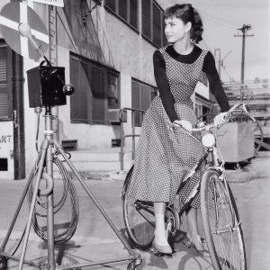 Audrey Hepburn stops her bike.