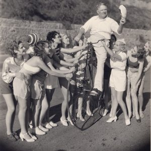 W.C. Fields rides a high-wheel bike.