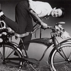 Robin Williams rides a bike.