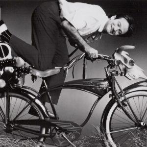 Robin Williams rides a bike.
