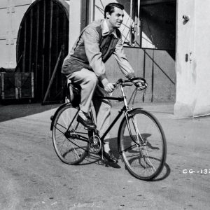 Cary Grant rides a bike.