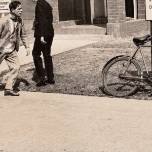 Norman Wisdom, slouching towards bicycle.