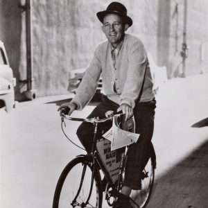 Bing Crosby rides a bike.
