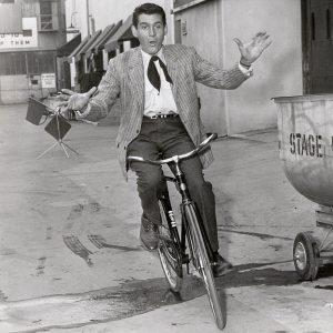 Gene Barry rides a bike.