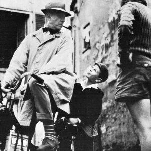 Jacques Tati and Alain Bécourt ride a bike.