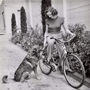Gene Tierney rides a bike, shakes a paw.