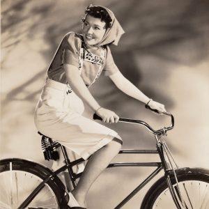 Penny Singleton rides a bike.