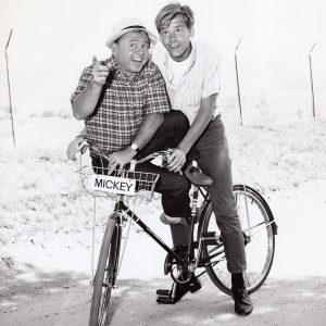 Mickey Rooney and Tim Rooney ride a bike.