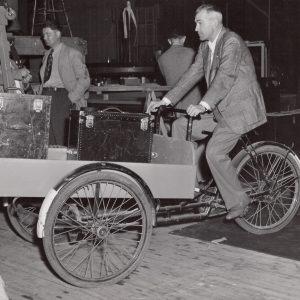 W.S. Van Dyke rides a cargo trike.