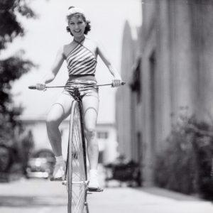 Jean Parker rides a high-wheel bike.