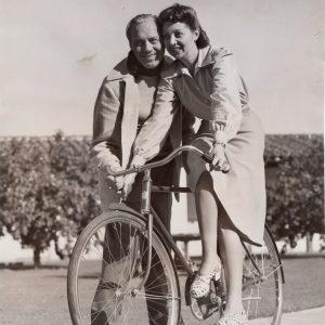 Mary Livingstone, aka Mrs. Jack Benny, rides a bike — with Benny lending a hand.