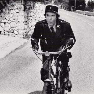 Roberto Benigni rides a bike.
