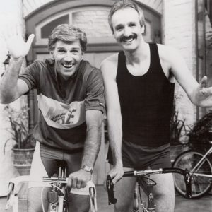 Gary Collins and Michael Gross ride bikes.